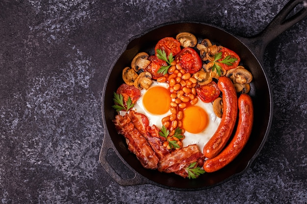 Traditional full english breakfast with fried eggs, sausages, beans, mushrooms, grilled tomatoes and bacon.