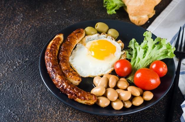 目玉焼き、ソーセージ、豆、トマトを皿に盛り付けた伝統的なフルイングリッシュブレックファースト、