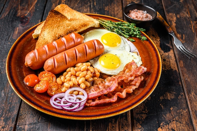 Традиционный полный английский завтрак с яичницей, сосисками, беконом, фасолью и тостами.