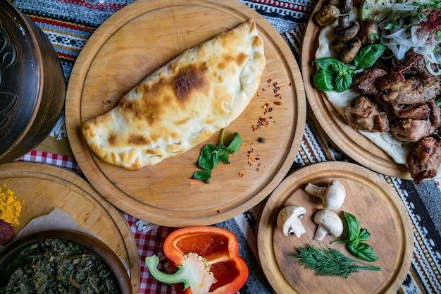 テーブルの上の伝統的なグルジアのアジャリアハチャプリとコルクハチャプリ。自家製ベーキング