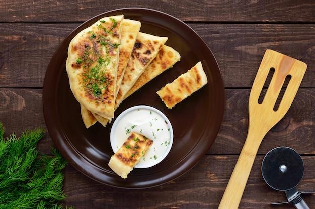 Традиционный грузинский сырный пирог - хачапури, сливочный соус. национальная кухня грузии. вид сверху.