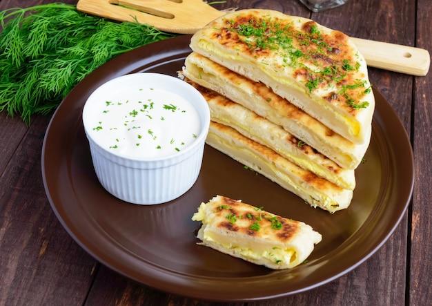 Традиционный грузинский сырный пирог - хачапури, сливочный соус. национальная кухня грузии.