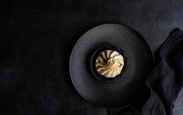 Традиционный грузинский демплинг, известный как хинкали по-грузински на черной тарелке, подается с черной салфеткой на черном бетоне с копией пространства