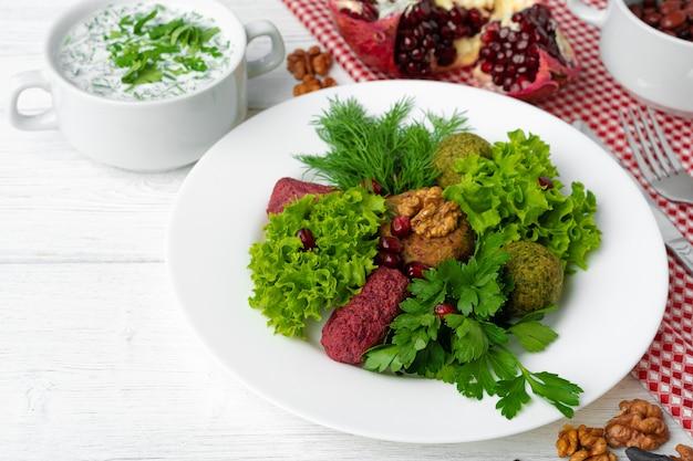 Традиционная грузинская закуска пхали подается с листьями салата и зеленью
