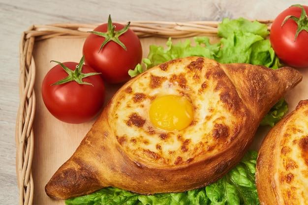 Traditional georgian dish of cheese-filled fragrant bread on a wooden table. adjaran open khachapuri. Premium Photo