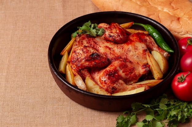 전통적인 그루지야 어 요리, 담배 치킨, 감자, 나무 테이블에 위에서 볼 수 있습니다.