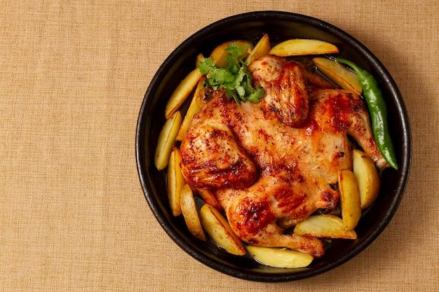 나무 테이블에 감자와 함께 전통적인 그루지야 요리, 담배 치킨, 위에서 볼