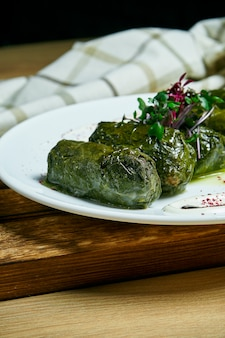 Traditional georgian dolma in grape leaves staffed with rice and meat on white plate on wooden table.. .