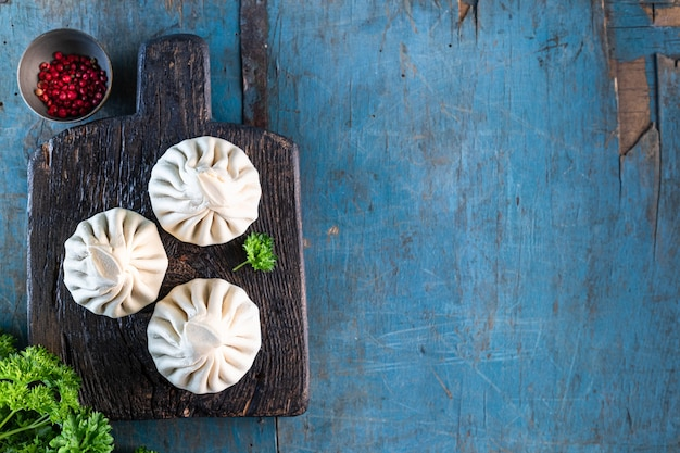 ヒンカリと呼ばれる伝統的なグルジア料理。古い青い木製のテーブルに自家製のヒンカリ。スペースをコピーします。上面図