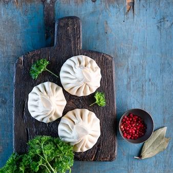 ヒンカリと呼ばれる伝統的なグルジア料理。古い青い木製のテーブルに自家製のヒンカリ。平方