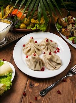 Традиционная грузинская еда хинкали на белой тарелке с гранатом, вилкой, зеленью