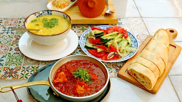 Традиционные грузинские блюда с популярными блюдами, которые подаются на плиточном столе в этническом узоре