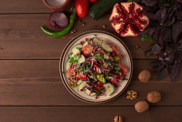 Традиционный грузинский салат, свежие овощи, с ореховой заправкой, специями, зеленью, зернами граната, горизонтальный, без людей. фото высокого качества