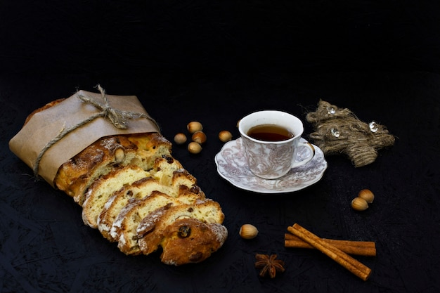 Traditional german christmas pastry - stollen on a black background with fir branches, spi