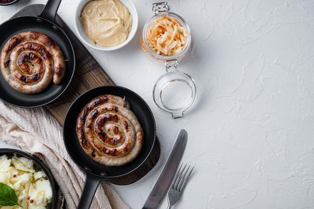 鋳鉄製フライパンにマッシュポテトとザワークラウトを入れた伝統的なドイツのソーセージ