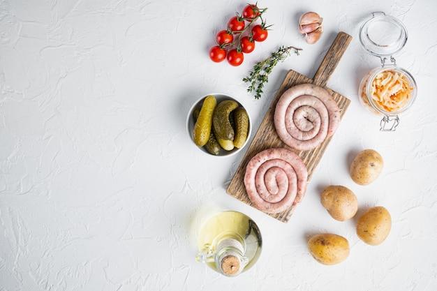 Традиционные немецкие колбаски с картофельным пюре и квашеной капустой, на белом фоне, плоский вид сверху,