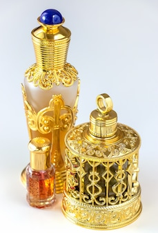 Traditional golden ornate flask of arabian oud oil perfumes. isolated white background.