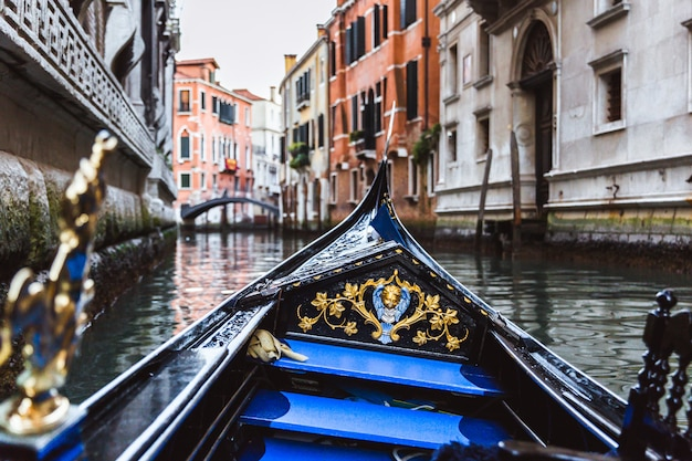 Traditional gondola on narrow canal on sunset in venice, italy