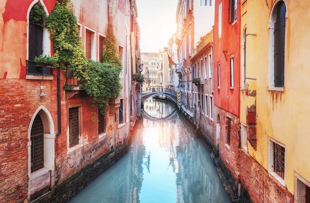 Традиционные гондолы на узком канале между красочными историческими домами в венеции, италия