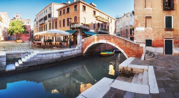 イタリア、ベニスのカラフルな歴史的家屋の間の狭い運河にある伝統的なゴンドラ