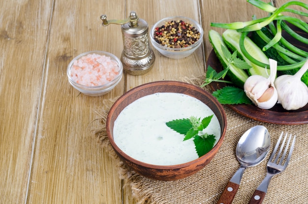Traditional greek dip sauce or dressing tzatziki prepared with grated cucumber, yogurt, olive oil and fresh dill on wooden table in ceramic bowl.