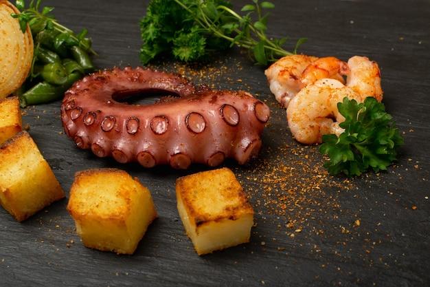 エビと野菜を添えた黒い石のプレートで伝統的なギリシャのグリルシーフード。新鮮な野菜とスパイスが入ったおいしいバーベキュータコの触手