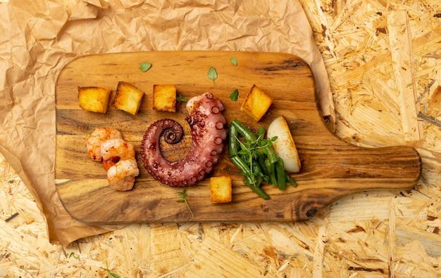 エビと野菜の素朴なスタイルで提供される木製のカットボード上の伝統的なギリシャのグリルシーフード。新鮮な野菜の上面図とおいしいバーベキュータコの触手