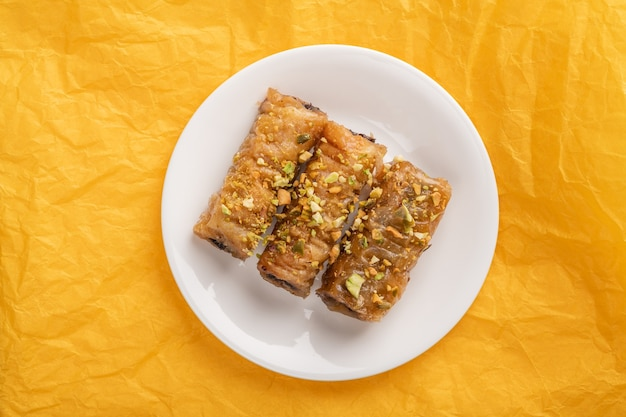 Сарагли из традиционной греческой выпечки в белой тарелке на желтой бумажной поверхности, вид сверху