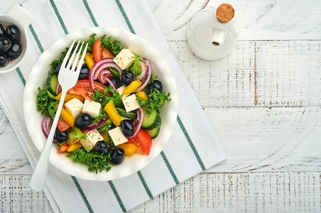 신선한 오이, 토마토, 달콤한 고추, 상추, 붉은 양파, 페타 치즈, 올리브 오일을 하얀 접시에 넣은 전통적인 그리스 샐러드. 건강에 좋은 음식, 최고 전망.