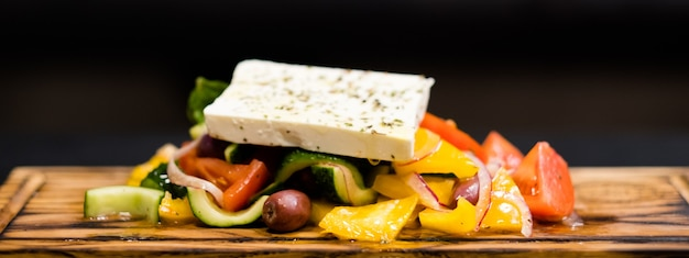 伝統的なギリシャ風サラダのレシピ。エキストラバージンオイルで味付けした肉野菜、カラマタオリーブ、フェタチーズ。