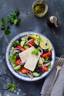 Традиционный греческий салат. вегетарианское блюдо со свежим салатом, оливками, перцем, огурцами, луком и сыром фета. на темном деревенском бетонном фоне. вид сверху.