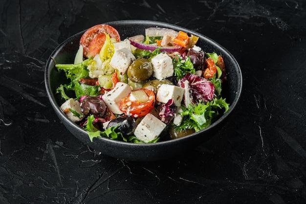 Традиционный греческий салат со свежими овощами, сыром фета и оливками на черном столе