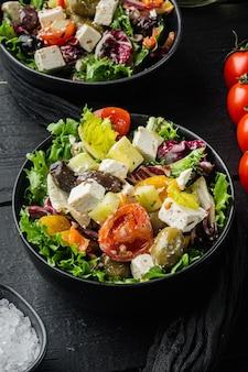 검은 나무 테이블에 신선한 야채, 죽은 태아, 올리브를 곁들인 전통적인 그리스 샐러드