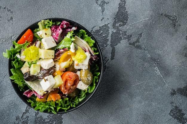 Традиционный греческий салат со свежими овощами, фетой и оливками, на сером фоне, плоский вид сверху с местом для текста