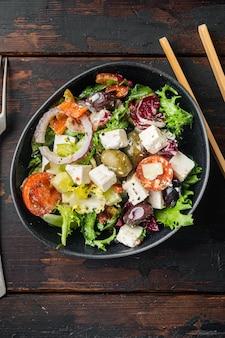 Традиционный греческий салат со свежими овощами, фетой и оливками, на фоне старого темного деревянного стола, плоская планировка, вид сверху
