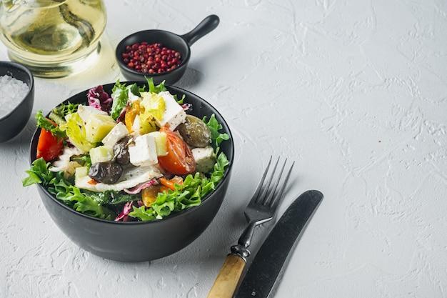 Традиционный греческий салат со свежими овощами, сыром фета и оливками, на белом столе