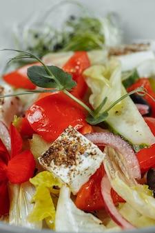 新鮮な野菜、フェタチーズ、オリーブを使った伝統的なギリシャ風サラダ。上面図。セレクティブフォーカス。