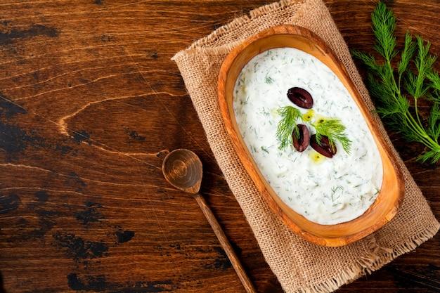Традиционный греческий соус или соус цацики, йогурт, огурец, укроп, чеснок и соленое масло в деревенской деревянной миске на деревянном фоне. деревенский стиль. выборочный фокус. вид сверху.
