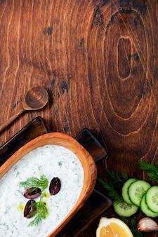 Традиционный греческий соус цацики в оливковой деревянной миске на старой деревенской поверхности