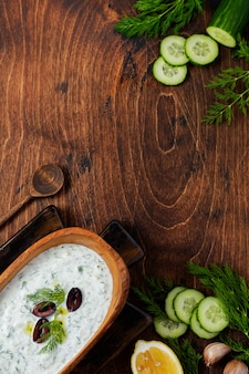 Traditional greek sauce tzatziki in olive wooden bowl on old rustic surface