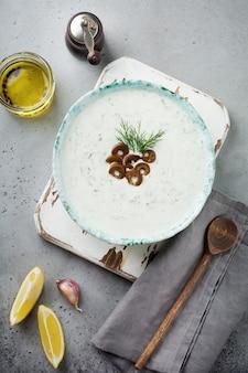 伝統的なギリシャのソースザジキ。灰色のコンクリート表面のセラミックボウルにヨーグルト、キュウリ、ディル、ニンニク、塩油
