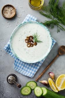 Традиционный греческий соус цацики. йогурт, огурец, укроп, чеснок и соленое масло в керамической миске на сером каменном или бетонном фоне