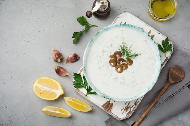 Традиционный греческий соус цацики. йогурт, огурец, укроп, чеснок и соленое масло в керамической миске на сером каменном или бетонном фоне.