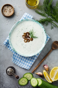 Traditional greek sauce tzatziki. yoghurt, cucumber, dill, garlic and salt oil in a ceramic bowl on a gray stone or concrete background