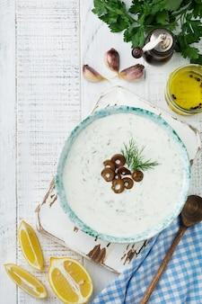 伝統的なギリシャのソースザジキ。軽い木の表面のセラミックボウルにヨーグルト、キュウリ、ディル、ニンニク、塩油