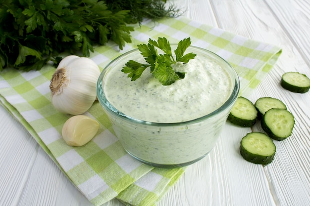 Traditional greek yogurt with cucumber on the white  wooden background.closeup.