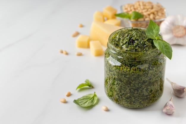 Традиционный зеленый соус песто в банке и ингредиенты на мраморном столе с копией пространства