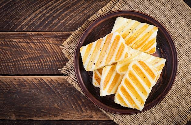 Традиционный сыр халлуми на гриле на тарелке на деревянных фоне. вид сверху, вверху