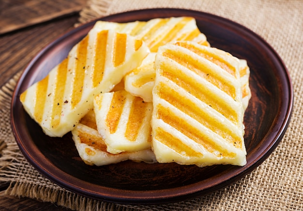 Traditional grilled halloumi cheese on plate on wooden background.