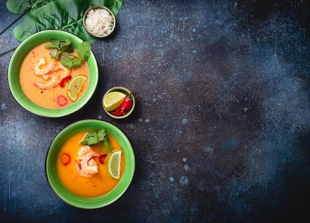 Традиционный здоровый тайский суп том ям с креветками, лаймом, кориандром в миске на деревенском фоне с белым рисом, накладной выстрел. аутентичная тайская кухня с копией пространства